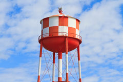 Water tower with red and white stripes. (blue sky background stock photography