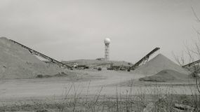 A water tower and a sand making plant. A monochrome image of moon-like sand and gravel making plant with a ball of water tower in the distance Stock Image