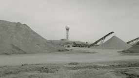 A water tower and a sand making plant. A monochrome view of a moon-like sand making plant with a ball of water tower in the distance Stock Photography