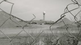 A water tower and a sand making plant through a wire-fence. A monochrome view of a moon-like sand making plant with a ball of water tower in the distance Stock Photos