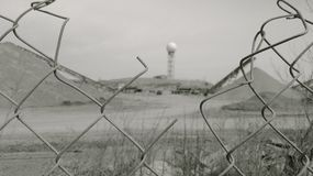 A water tower and a sand making plant through a wire fence. A monochrome view of moon-like construction sight with a ball of a water tower in distance, and a Stock Image