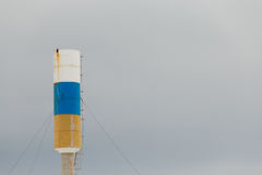 Water tower with white, blue and orange stripes. Stock Photos