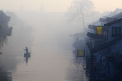 Water town morning. Slight fog raise at the water town morning. One small boat run on the river. The whole screen form a beautiful picture. This place names Stock Photos