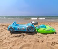 Water toys for little kids at a beautiful beach with no people. Inflatable water toys for little kids at a beautiful beach with no people, funny and playtime royalty free stock photo