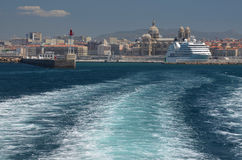 Water track leading to Marseille Cathedral and a cruise ship. Water track behind a small boat leading to a large cruise ship docked under byzantine Marseille Royalty Free Stock Photos