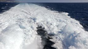 Water trail foaming behind a ferry boat in Atlantic ocean. Between Canary islands, Spain. Ferry from Fuerteventura island on the background to Gran Canaria stock footage