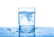 Water in transparent glass with drops and bubbles isolated over. White, blue background, close up Royalty Free Stock Images