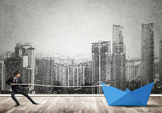 Water transporation concept. Successful businessman pulling with rope paper boat Stock Photos
