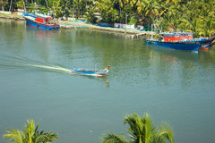 Water transport of India 1. Water transport of India. Passenger flat-bottomed boat under canopy and two moored boats small move along canal surrounded by palm Stock Photo
