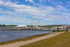The National Harbor coastline and pier with Ferris in Oxon Hill, Maryland, USA. Water transport pier services visitors coming from Washington DC Stock Images