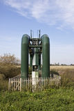 Water treatment pipes. Some green water treatment pipes spanning the river Stock Photo