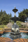 Water trickling over a fountain on a sunny day at Shore Acres State Park, Oregon. This statue is the centerpiece of a botanical garden on the Oregon coast. The stock image
