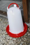 Water trough. Red and white plastic water trough in cage Royalty Free Stock Photography