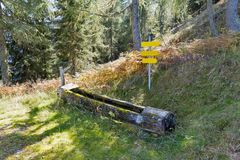 A water trough for wildlife in Alps mountains. A water trough for wildlife with road signs in Alps mountains, Western Carinthia, Austria Stock Photography