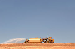 Water truck at construction site. A view of a large water truck at a construction site on a hot blue clear sky day spraying water to hold dust down Royalty Free Stock Photography