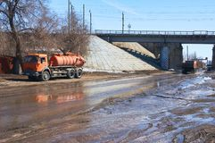 An orange-colored water truck stands by the road near the bridge. royalty free stock photo
