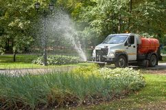 Water truck sprays water on garden of public park. Sunny warm autumn day. stock image