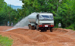 Water truck sprays water on  new road construction project. Royalty Free Stock Images
