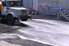 Water truck watering the asphalt at a manufacturing plant for du. St suppression royalty free stock image