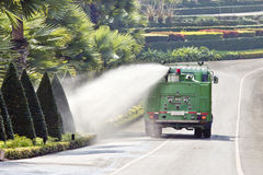 Water truck watering bush in park Royalty Free Stock Images