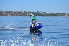 Water tubing skiing teen boy. Male teen water skiing tubing in the river Royalty Free Stock Image
