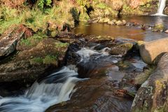 Water tumbles down small cascades at Three Shires Head stock photography