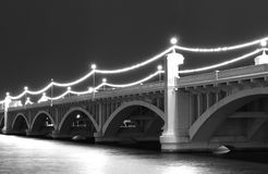 Water under a bridge. Black and white photo of a bridge with water running under it and lights reflection on water stock image