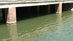 Water under bridge. Water flowing under concrete bridge stock footage