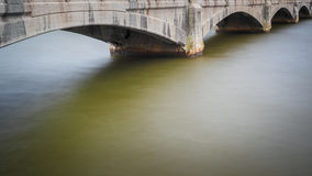 Water Under The Bridge. A long exposure of the river flowing under the bridge stock image