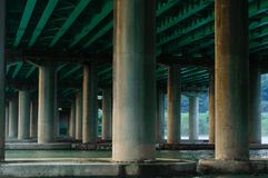Water Under a Bridge. The underside of a bridge with green beams and the river flowing underneath. Support columns are visible and there are trees in the stock photo