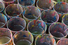 Water used to wash paint brushes stained with paint. Royalty Free Stock Photos