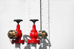 Water Valves. Two Red metal water valves and golden brass caps against a white metal wall. Fire protection Royalty Free Stock Image