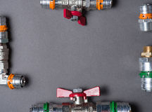Water valves with fittings on grey, frame Royalty Free Stock Photo