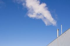 Water vapor or steam from a factory. Water vapor or steamin front of a blue sky  from a factory Royalty Free Stock Image