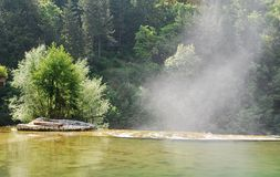 Water Vapour Rising From Jajce Waterfall. Water Vapour from Pliva Waterfall rising by a man made island in the River Pliva as it flows over Pliva Waterfall in Stock Photo