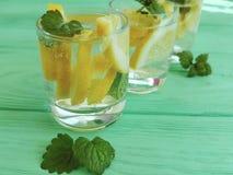 water verse citroen, munt op een groene houten zomer als achtergrond stock afbeeldingen