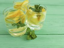 Water verse citroen, munt traditioneel op een groene houten zomer als achtergrond royalty-vrije stock foto