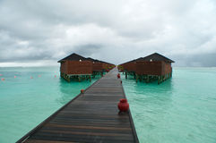 Water villa walkway maldives. Water villas along a wooden walkway, with a beautiful green ocean and a stormy looking sky above Stock Photo