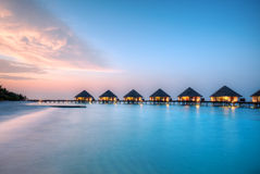 Water villas on Maldives resort island in sunset Royalty Free Stock Images