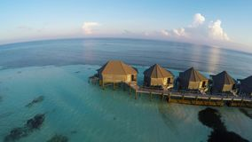Water villas in the ocean with steps into turquoise lagoon, Kuredu, Maldives. Aerial view of luxurious water villas in Maldives, Kuredu stock footage