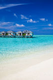 Water villas in the ocean and white sandy beach. Water villas in the tropical ocean and white sandy beach Stock Images
