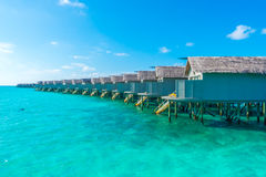 Water villas over calm sea  in tropical Maldives island . Stock Images