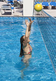 Water Volleyball. A woman jumps high while playing water volleyball Royalty Free Stock Photo