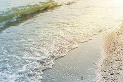 Water wave over sand beach. And sun reflections Royalty Free Stock Photography