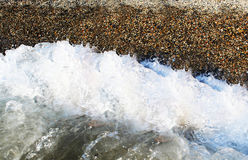 Water wave with pebble ashore Royalty Free Stock Image