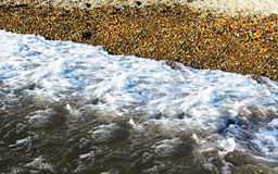 Water wave with pebble ashore Royalty Free Stock Images