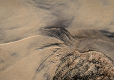 Abstract pattern on the beach sand. Water waves on beach created abstract pattern with sand rock at the bottom royalty free stock photos