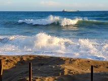 Rough sea on the sandy beach. Water waves on the beautiful sandy beach Stock Photos