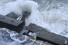Water waves hit the quayside and destroy the road. High waves caused by a heavy storm hit the quayside and destroy a paved road there stock photos