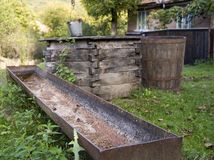 Water Well. A dried out water trough with a water well and a barrel in the background Stock Photos